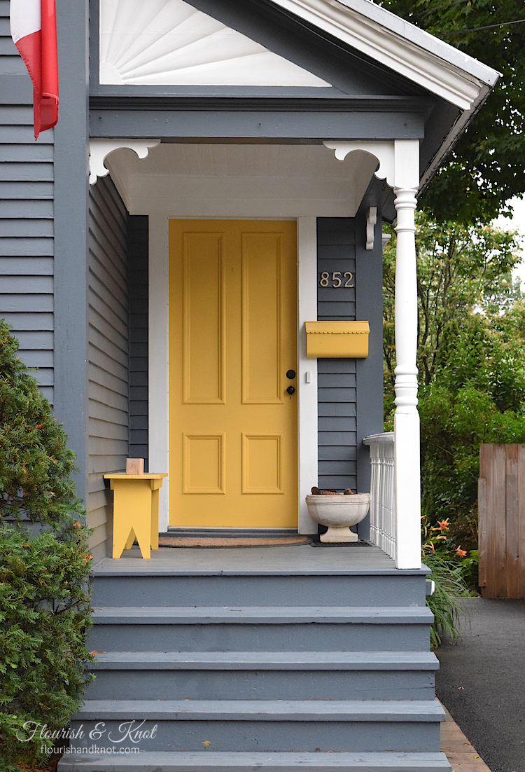 Beautifully restored heritage home in Fredericton, New Brunswick, with a grey facade and a yellow door
