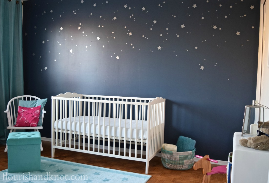 Navy, turquoise, pink, and white Harry Potter nursery with starry accent wall | flourishandknot.com