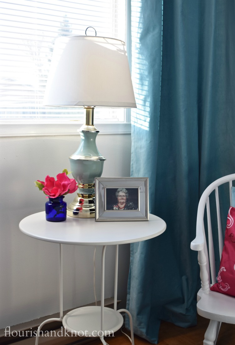Turquoise and gold lamp, pink flowers, and a silver-framed photograph in our Harry Potter nursery | flourishandknot.com