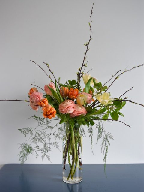 Springtime floral arrangement in a tall cylinder vase | palette of coral, pink, yellow, green, and orange | ranunculus, tulips, cherry branches