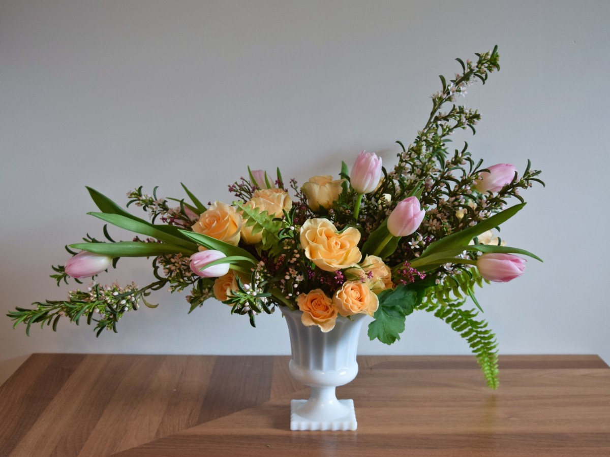 Romantic spring centrepiece in pink and peach palette in vintage milk glass pedestal vase | Flourish & Knot