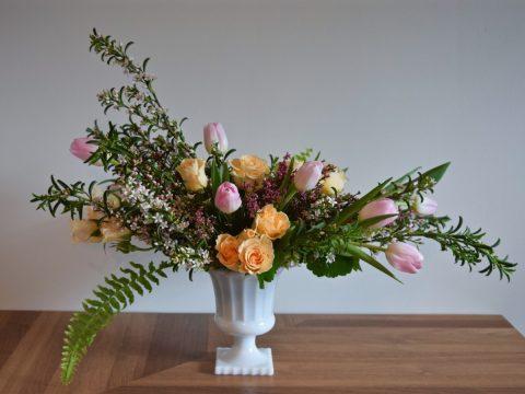 Romantic spring centrepiece in pink and peach palette in vintage milk glass pedestal vase | Flourish & Knot