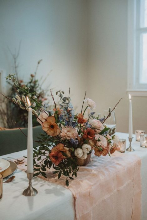 Spring centrepiece with butterfly ranunculus, ranunculus, pussy willows, delphinium, lisianthus, and branches in a blush, burgundy, and blue palette | Montreal wedding florist