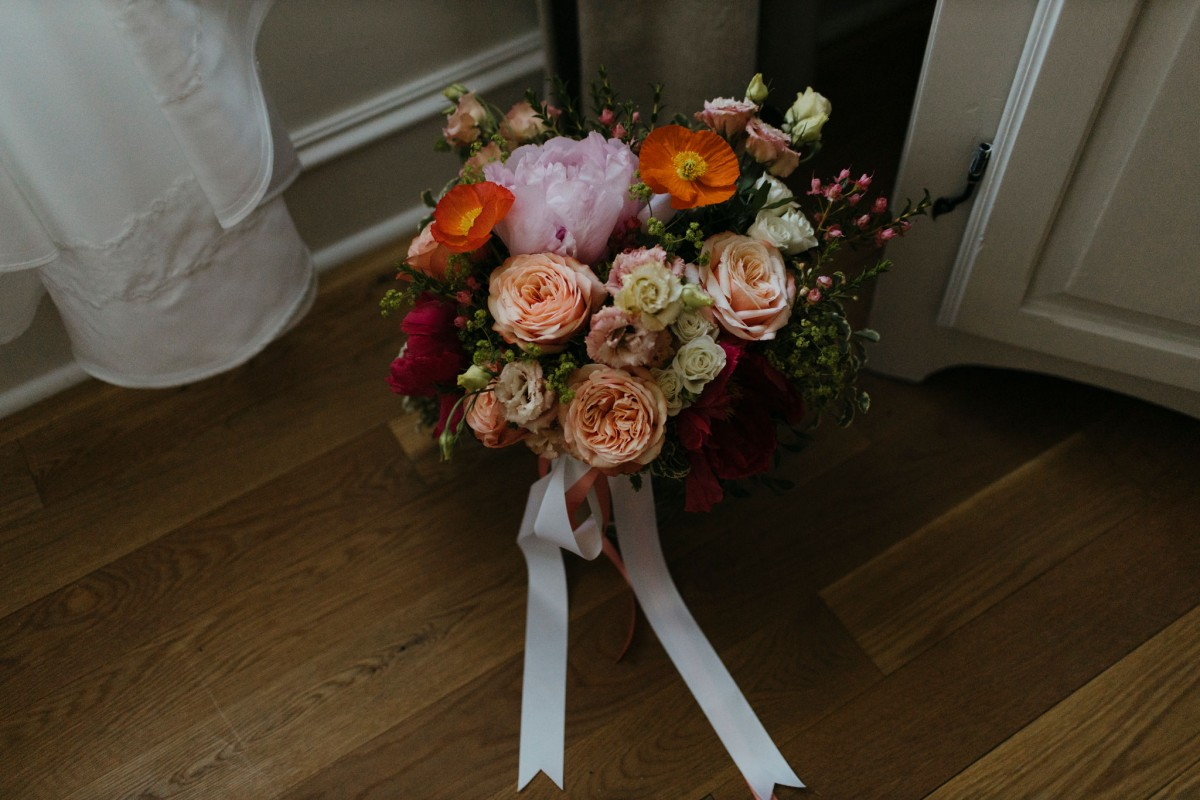 Spring bouquet with coral, apricot, pink, and orange tied in garden-gathered style tied with flowing satin ribbons | Flourish & Knot | Montreal wedding florist | Photo by Naomie Houle
