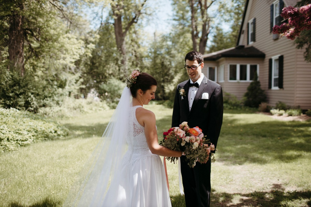 Bride and groom looking at wedding bouquet of early peonies, poppies, and garden roses | Bouquet by Flourish & Knot | Photo by Naomie Houle
