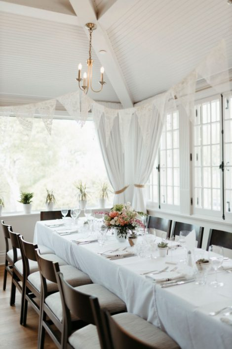 Wedding reception with long banquet tables at the Auberge Willow Inn in Hudson, Quebec | Low compote-style centrepieces with coral and apricot tones | Flourish & Knot | Montreal wedding florist | Photo by Naomie Houle
