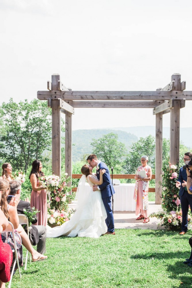 Floral ceremony arch with pink peonies, climbing greenery | Photo by Cassandre Poblah