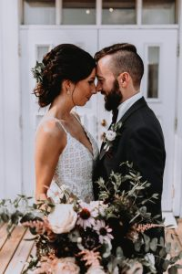 Bride and groom with heads together, groom with white lisianthus boutonniere and bride with wildflower bouquet | Photo by Andréanne Thériault