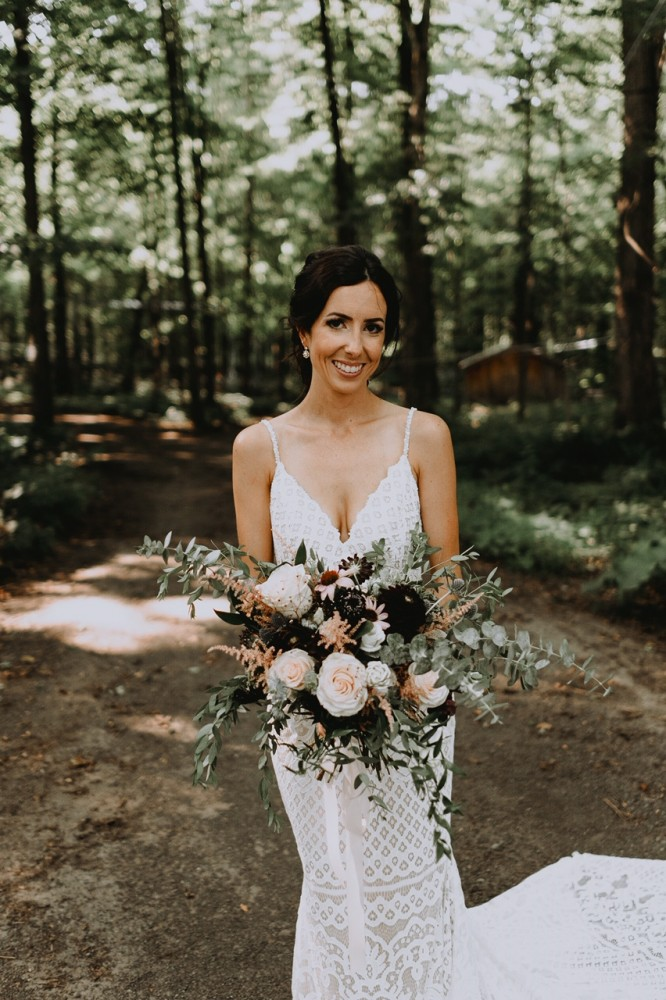 Bride with organic wildflower-style bouquet with marzipan roses, burgundy dahlias, and pink astilbe | Photo by Andréanne Thériault