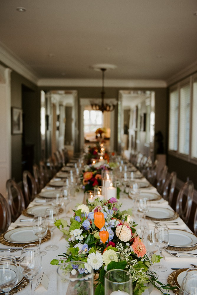 Long wedding table setting with colourful fall florals by Flourish & Knot, pillar candles and gold chargers | Photo by L'Orangerie Photography | Florals by Montreal wedding florist Flourish & Knot