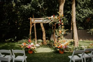 Colourful chuppah with fall planters and greenery and flowers climbing up chuppah | Photography by L'Orangerie Photographie | Foam-free floral installation by Flourish & Knot | Foam-free floral installation | Dahlias, zinnias, roses