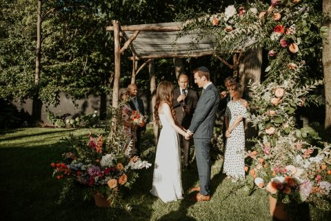 Colourful chuppah with fall planters and greenery and flowers climbing up chuppah | | Photography by L'Orangerie Photographie | Foam-free floral installation by Flourish & Knot | Foam-free floral installation | Dahlias, zinnias, roses