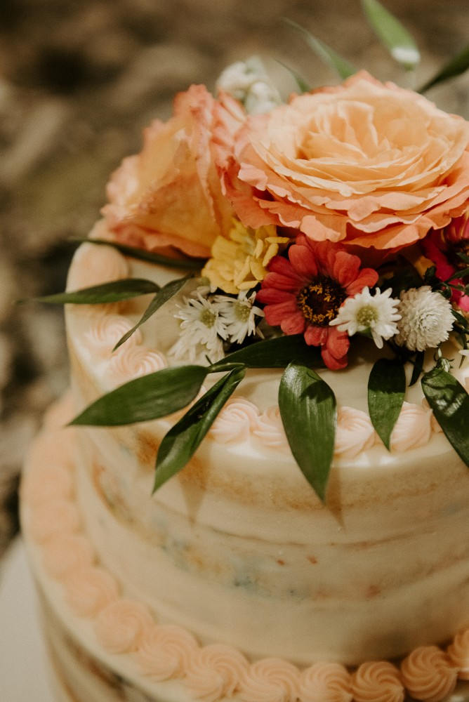 Cake flowers with free spirit roses, zinnias, gomphrena | Colourful chuppah with fall planters and greenery and flowers climbing up chuppah | | Photography by L'Orangerie Photographie | Flowers by Flourish & Knot