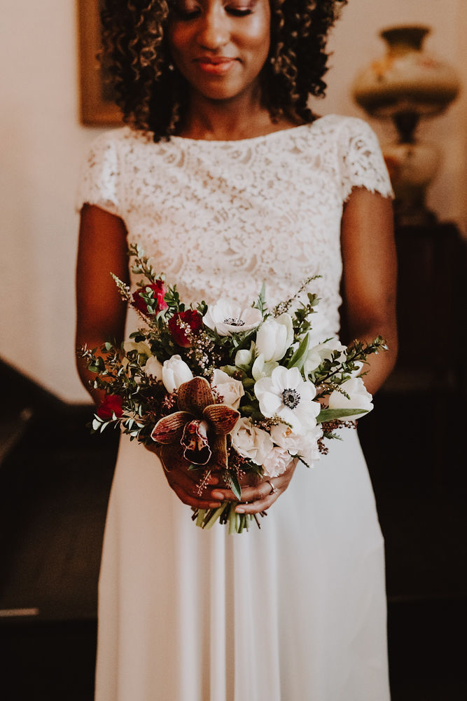Bridal bouquet in burgundy, brown, white, red, and green | Orchid anemone tulip and hellebore bouquet | winter wedding bouquet | Florals by Flourish & Knot | Photo by Photographie M'Vivre | Gown by Robelie