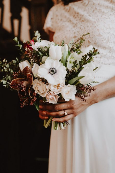 Winter wedding bouquet of anemone, tulips, hellebore, spray roses, and cymbidium orchid | Burgundy, blush, and white winter wedding bouquet | Florals by Flourish & Knot | Photography by Photographie M'Vivre | Maison Trestler | Gown by Robelie | Makeup by Chrom Artistry