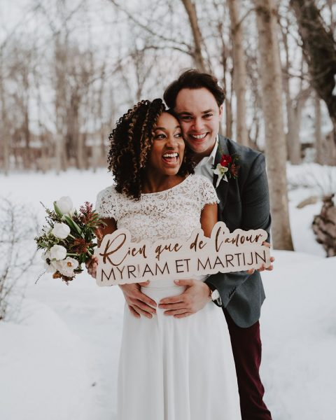 Winter wedding couple | Burgundy, red, and white winter wedding | Bridal bouquet of tulips, anemones, hellebore | Florals by Flourish & Knot | Photo by Photographie M'Vivre | Maison Trestler | Gown by Robelie | Makeup by Chrom Artistry | Signage by D Style Cut