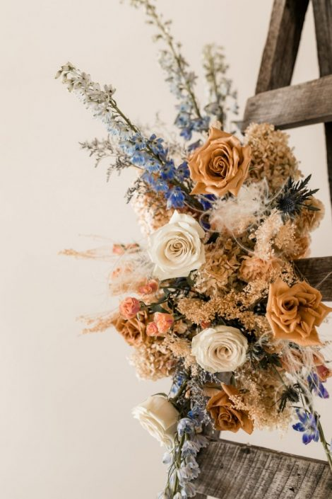 Modern boho wedding ceremony flowers | Foam-free floral installation for wedding arch or ceremony in terracotta and blue palette | Flourish & Knot