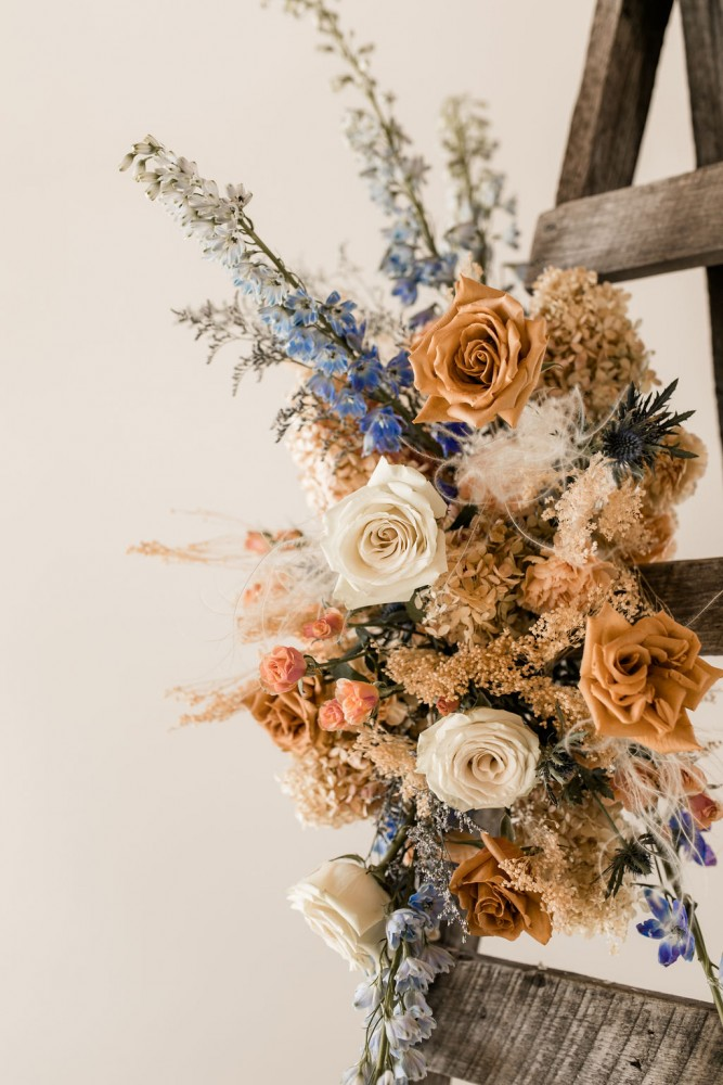 Foam-free floral installation for wedding arch or ceremony in terracotta and blue palette | Flourish & Knot