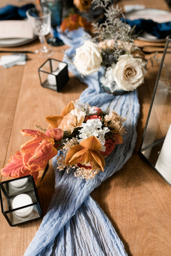 Bud vase centrepiece in terracotta and blush, with blue runner and black lanterns | Fine-art wedding editorial in terracotta and blue | Flourish & Knot | Photos by Kerstin Hahn