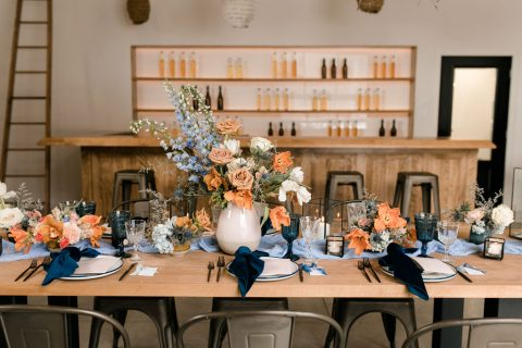 Wedding table setting with large centrepiece and bud vases in terracotta and blue palette | Ceramic bud vases | Flourish & Knot Floral Design Montreal | Montreal Wedding Florist | Apple Orchard Wedding | Verger du Flanc Nord | Lulucoeurdebeurre | Kerstin Hahn Photography | Blue and terracotta wedding