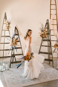 Wedding ceremony floral installation with ladders and draping in terracotta and blue palette | Flourish & Knot