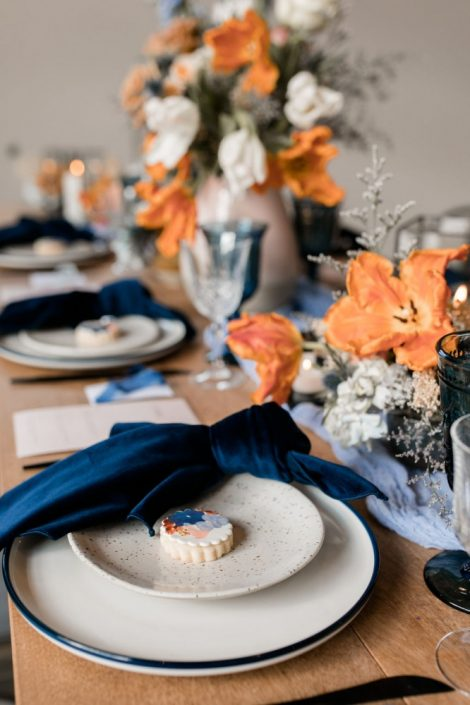 Terracotta, orange, and blue wedding palette | Wedding centrepiece with tulips and velvet napkins | Flourish & Knot